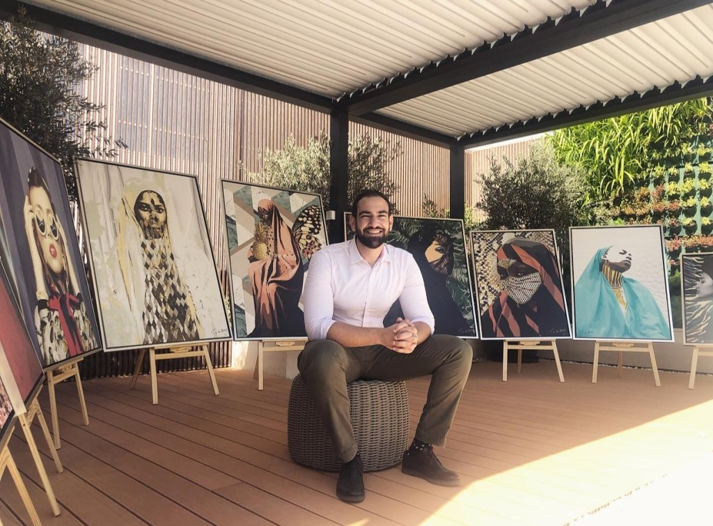 image of artist Tarek Shafagoj sitting in front of his painting collection Women of the East