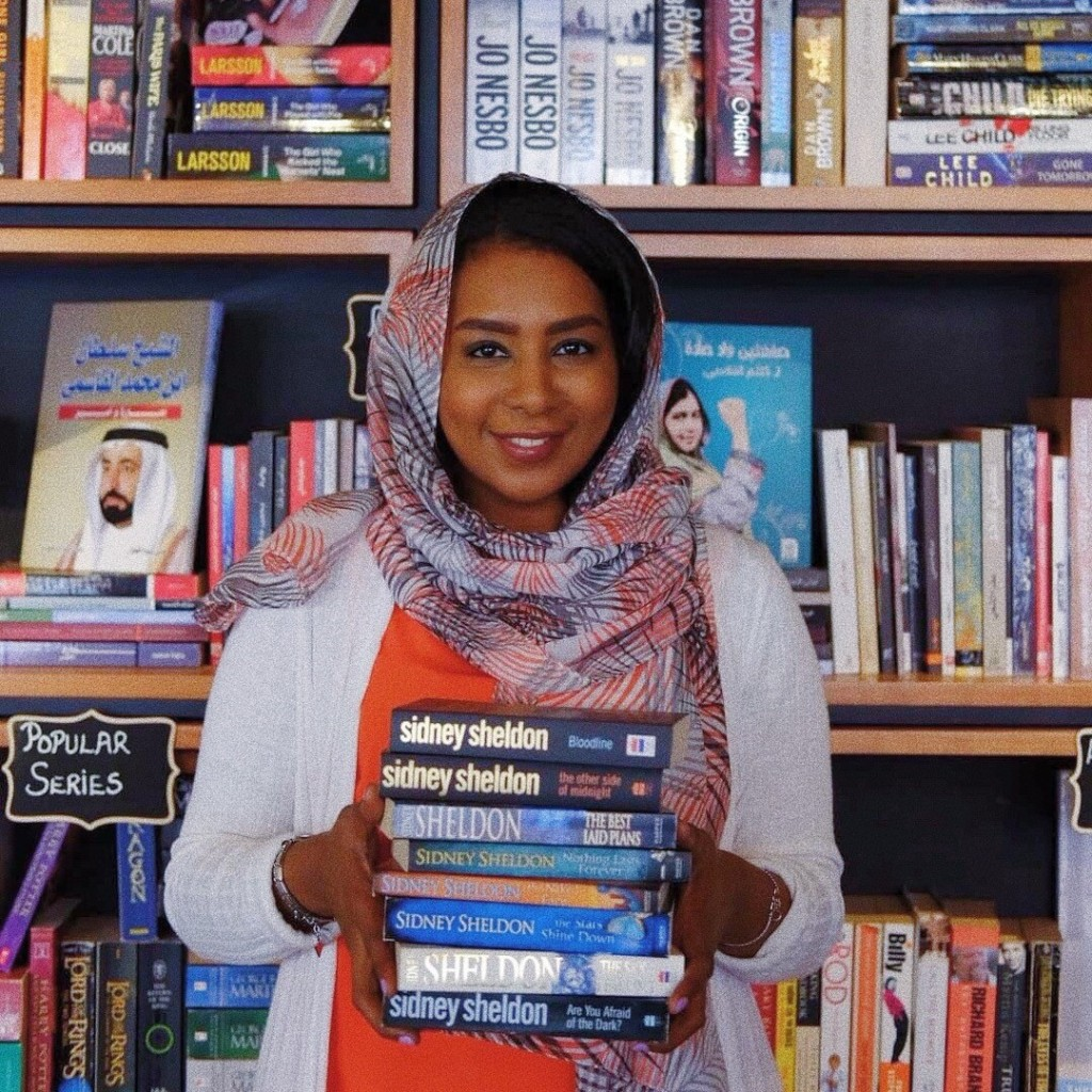 Nada standing in front of a library holding a stack of books wearing a white orange and black scarf and a white and orange blouse