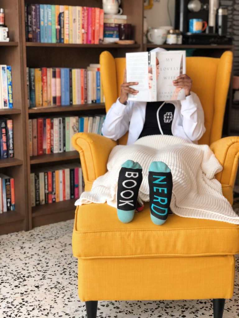 Nada sitting on a yellow chair holding up a book showing socks with book nerd written on them and a book library in the background