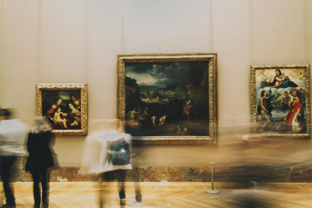 image of people standing in front of paintings in the louvre museum in paris